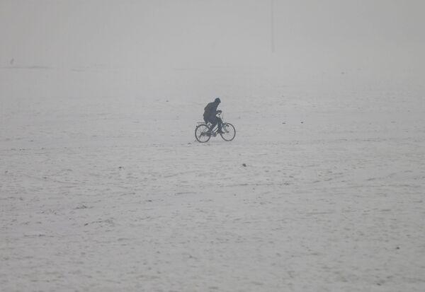 Мужчина едет на велосипеде по заснеженному Кабулу, Афганистан - Sputnik Узбекистан