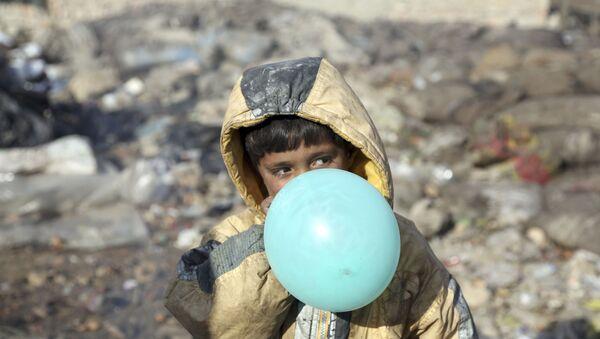Афганский мальчик надувает воздушный шарик, окраина Кабула, Афганистан, 2017 год - Sputnik Ўзбекистон