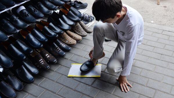 Мальчик примеряет обувь на рынке - Sputnik Узбекистан