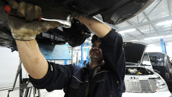 Сотрудник ремонтирует автомобиль - Sputnik Ўзбекистон