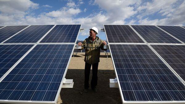 Мастер осматривает солнечные батареи - Sputnik Узбекистан