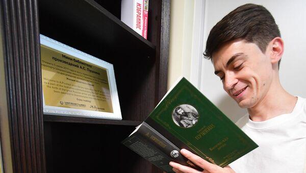 Молодой человек читает книгу из мини-библиотеки - Sputnik Узбекистан