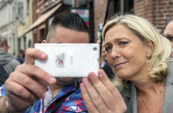 Frantsuzskiy politik Marin Le Pen vo vremya selfi so storonnikom  - Sputnik Oʻzbekiston