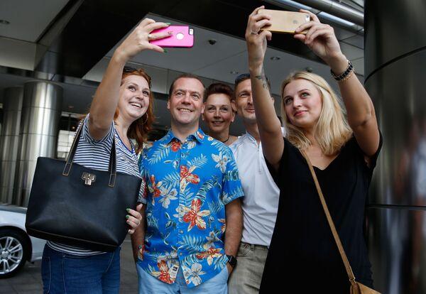 Premyer-ministr Rossii Dmitriy Medvedev vo vremya fotografirovaniya s rossiyskimi i ukrainskimi turistami v Kuala-Lumpure  - Sputnik Oʻzbekiston