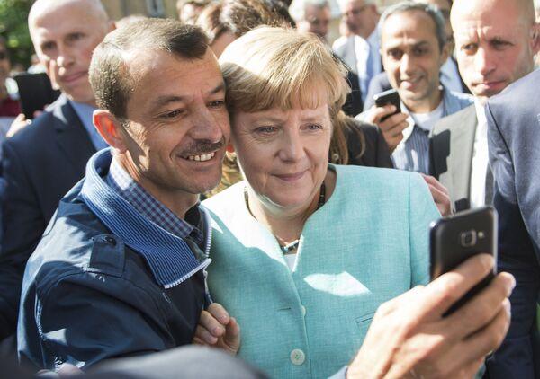 Bejenets delayet selfi s kantslerom Germanii Angeloy Merkel vo vremya yeye vizita v tsentr dlya novopribыvshix bejentsev v Berline - Sputnik Oʻzbekiston