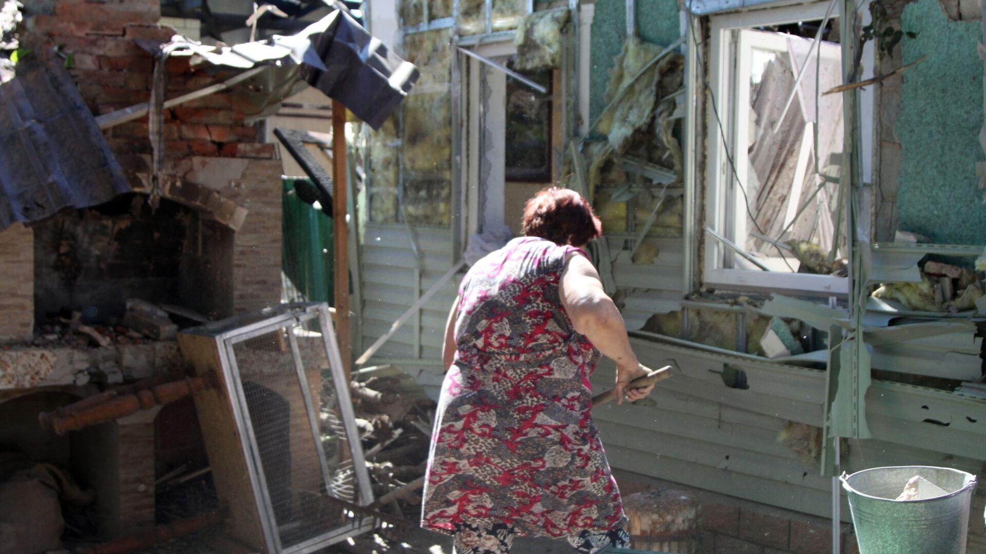 Женщина убирает мусор во дворе жилого дома в Донецке, пострадавшего в результате обстрела - Sputnik Ўзбекистон, 1920, 24.08.2021