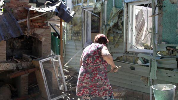 Женщина убирает мусор во дворе жилого дома в Донецке, пострадавшего в результате обстрела - Sputnik Ўзбекистон