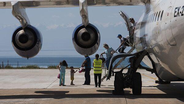 Пассажиры выходят с самолета в международном аэропорту в селе Тамчи, Иссык-Кульской области - Sputnik Узбекистан