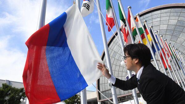 Вывешивание флага России у международного выставочного центра INTEX Osaka перед открытием саммита Группы двадцати в японской Осаке - Sputnik Ўзбекистон