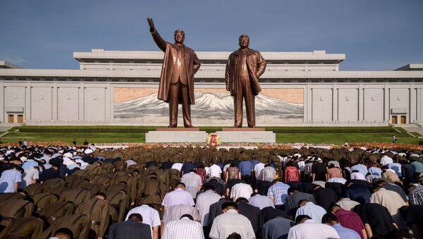 Жители Пхеньяна во время минуты молчания у памятника Ким Ир Сену и Ким Чен Иру в день отмечания 25-летия со дня смерти Ким ИМ Сена - Sputnik Ўзбекистон