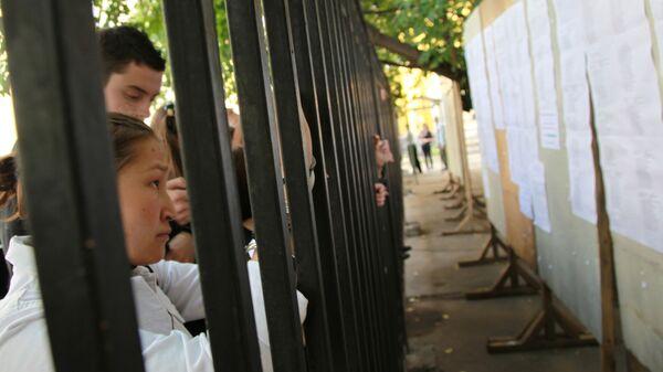 Абитуриенты стоят возле ограждения - Sputnik Узбекистан