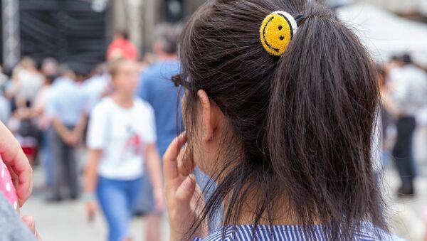 Резинка в виде эмодзи в волосах девушки в Кельне - Sputnik Ўзбекистон