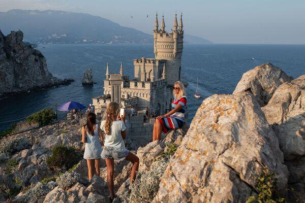 Отдыхающие фотографируются возле замка Ласточкино гнездо на береговой скале в поселке Гаспра в Крыму - Sputnik Узбекистан