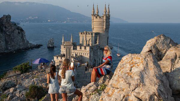 Отдыхающие фотографируются возле замка Ласточкино гнездо на береговой скале в поселке Гаспра в Крыму - Sputnik Ўзбекистон