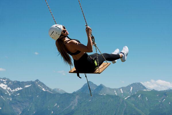 Девушка катается на тарзанке на горнолыжном курорте Роза Хутор в Сочи - Sputnik Узбекистан