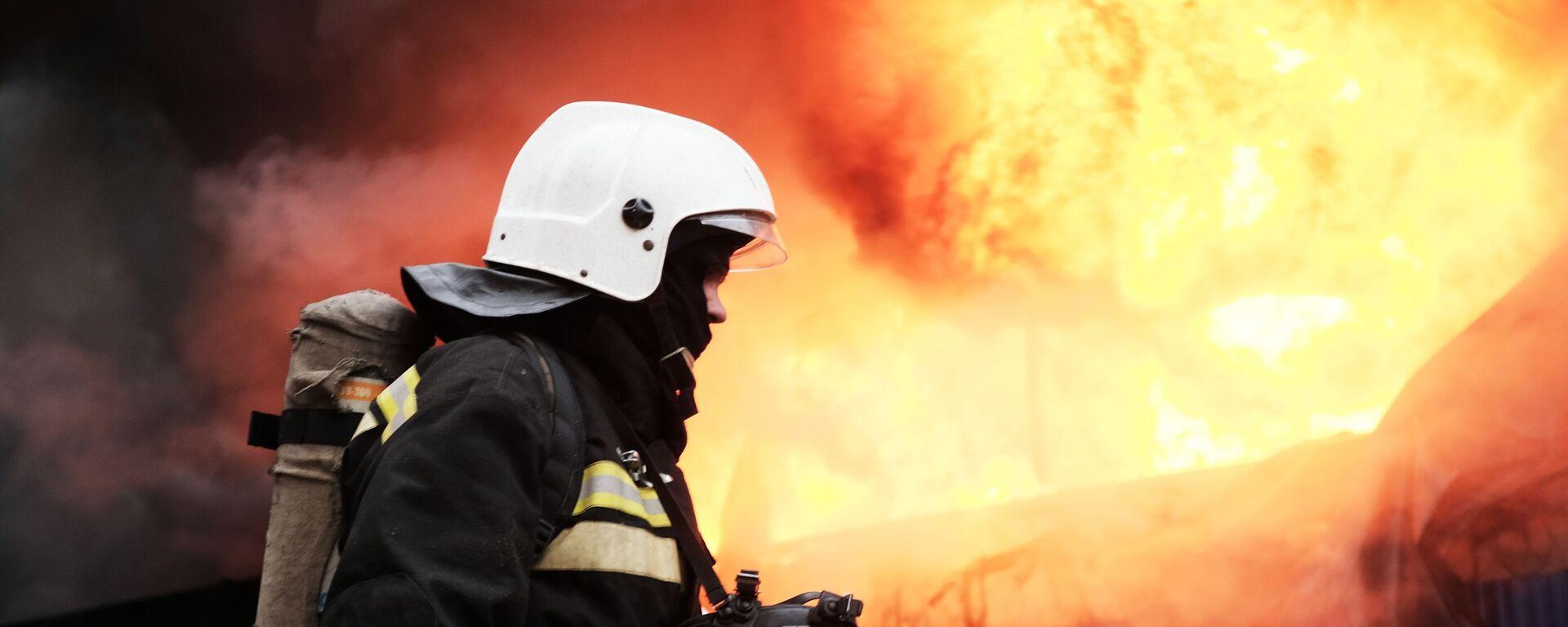 Сотрудник МЧС во время тушения пожара - Sputnik Узбекистан, 1920, 22.06.2021