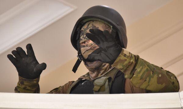 Сотрудник киргизских сил безопасности сдается после спецоперации в резиденции бывшего президента Киргизии Алмазбека Атамбаева  - Sputnik Узбекистан
