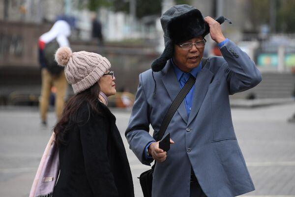 Иностранные туристы одевают теплые головные уборы на Манежной площади во время холодной погоды в Москве - Sputnik Узбекистан