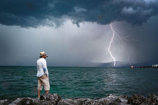 Мужчина на фоне молнии на горизонте озера Женева в Швейцарии - Sputnik Узбекистан