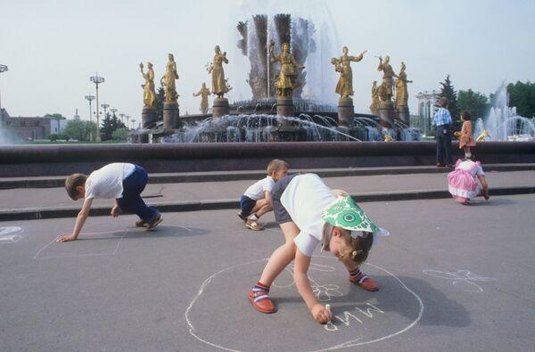 Дети рисуют мелом на асфальте у фонтана Дружба народов в Москве. 1984 - Sputnik Узбекистан