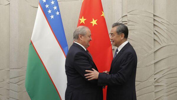 Министр иностранных дел Узбекистана Абдулазиз Камилов (слева) пожимает руку министру иностранных дел Китая Ван И, прибывшему на встречу в Пекин 19 августа 2019 года - Sputnik Узбекистан