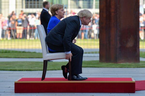 Канцлер Германии Ангела Меркель и премьер-министр Великобритании Борис Джонсон во время приветственной церемонии в рамках первого зарубежного визита Джонсона с момента вступления в должность - Sputnik Узбекистан