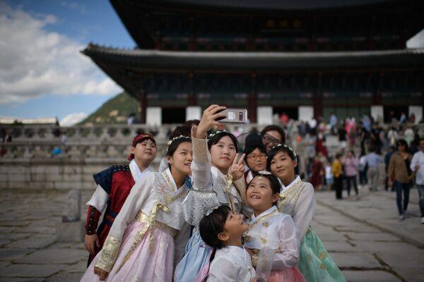 Одетые в традиционные корейские платья посетители фотографируются перед павильоном во дворце Кёнбоккун в Сеуле - Sputnik Узбекистан