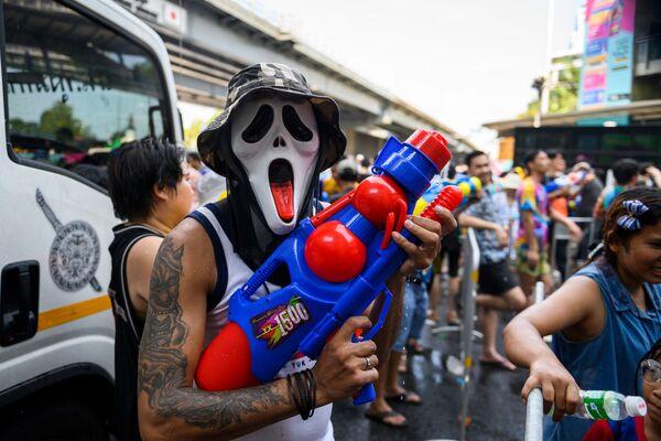 Человек в маске и с водяным пистолетом во время празднования буддийского нового года в Бангкоке - Sputnik Узбекистан