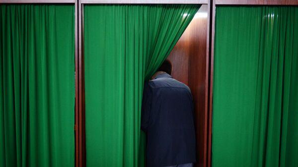Мужчина голосует на избирательном участке - Sputnik Ўзбекистон