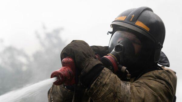 Сотрудник МЧС во время тушения пожара - Sputnik Ўзбекистон