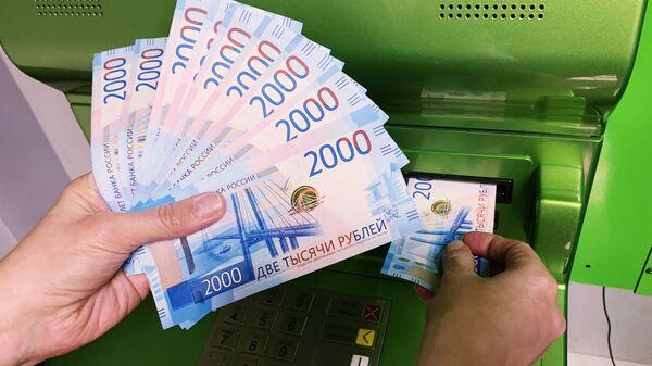 Клиент Сбербанка вносит наличные деньги в банкомат - Sputnik Узбекистан