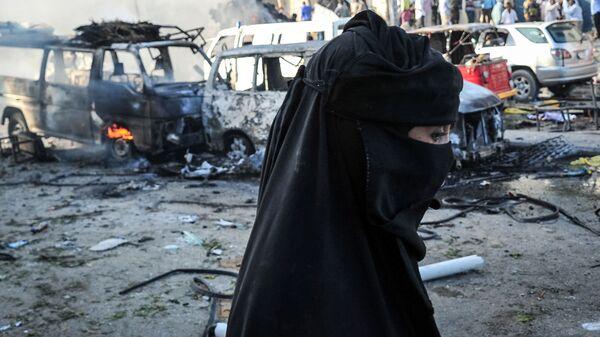 Женщина-мусульманка на фоне сгоревших машин. Иллюстративное фото - Sputnik Ўзбекистон