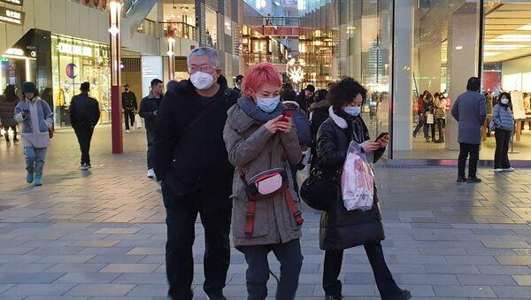 Прохожие в защитных масках на одной из улиц в Пекине - Sputnik Ўзбекистон