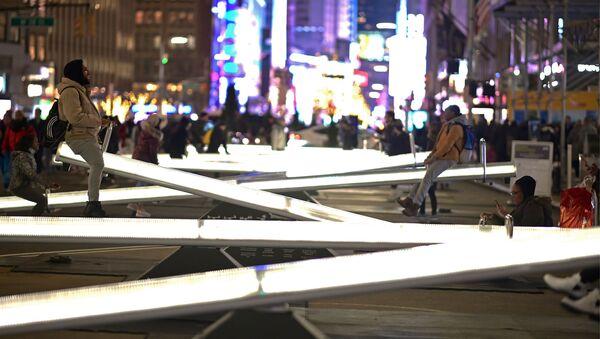 Люди катаются на светящихся качелях на Бродвее недалеко от Тайм-сквер в Нью-Йорке - Sputnik Узбекистан