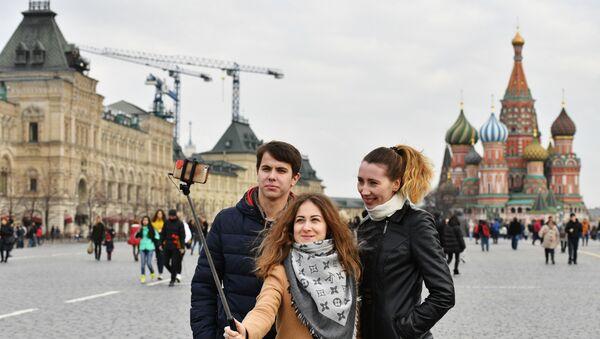 Туристы фотографируются на Красной площади в Москве. На дальнем плане справа - Покровский собор (храм Василия Блаженного). - Sputnik Ўзбекистон