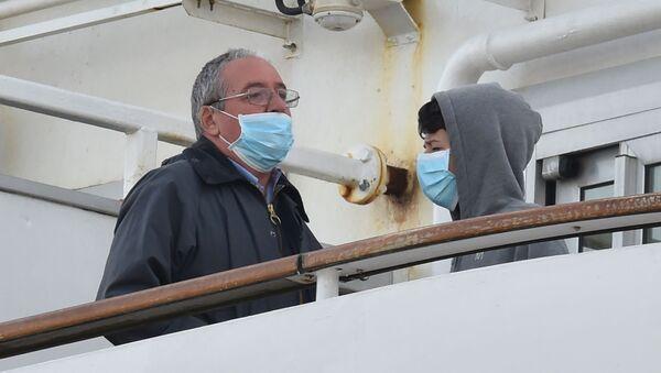 Пассажиры в медицинских масках на борту круизного лайнера Diamond Princes, помещенного в карантин у японского порта Йокогама - Sputnik Узбекистан