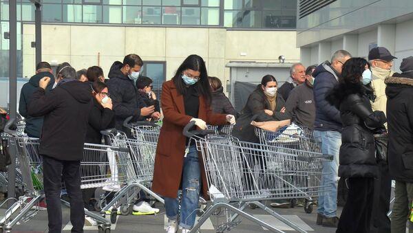 Люди стоят в очереди в супермаркете за пределами города Казальпустерленго, который был закрыт итальянским правительством из-за вспышки коронавируса на севере Италии - Sputnik Узбекистан