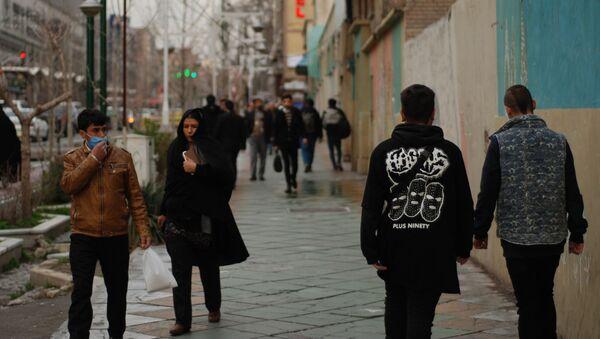 Жители Тегерана идут по одной из центральных улиц в медицинских масках - Sputnik Ўзбекистон