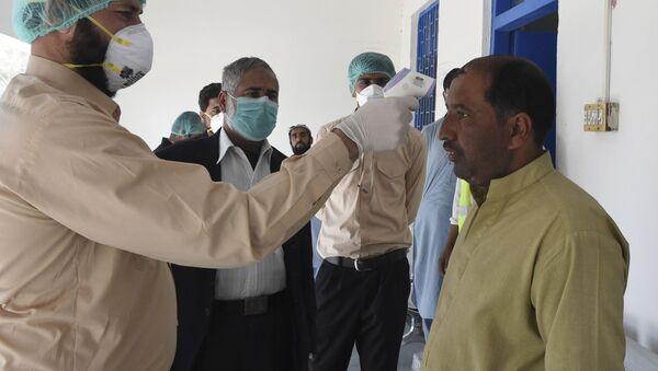 Врач проверяет температуру тела человека в городе Тафтан на пакистано-иранской границе - Sputnik Ўзбекистон