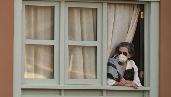Женщина смотрит из окна Costa Adeje Palace hotel на Тенерифе - Sputnik Ўзбекистон