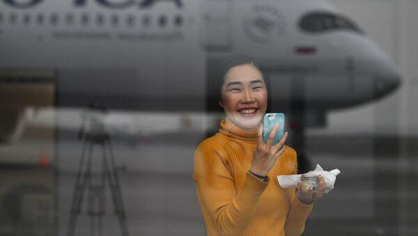Devushka fotografiruyet dalnemagistralnыy shirokofyuzelyajnыy passajirskiy samolet Airbus A350-900 aviakompanii Aeroflot - Sputnik Oʻzbekiston