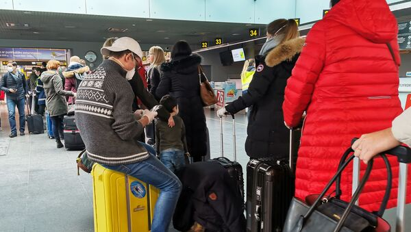 Пассажиры в медицинских масках в аэропорту Риги. - Sputnik Ўзбекистон