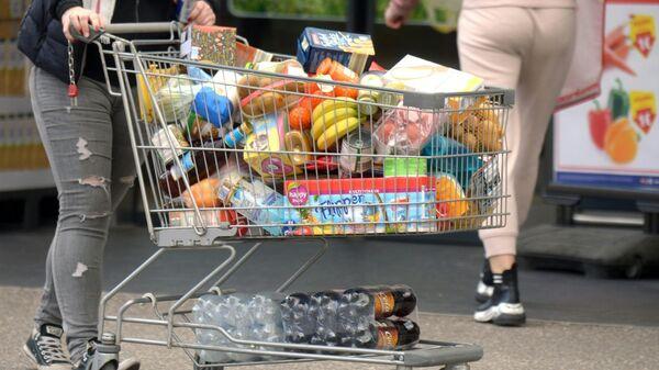 Pokupatel s telejkoy, napolnennoy produktami v supermarkete v Avstrii  - Sputnik Oʻzbekiston