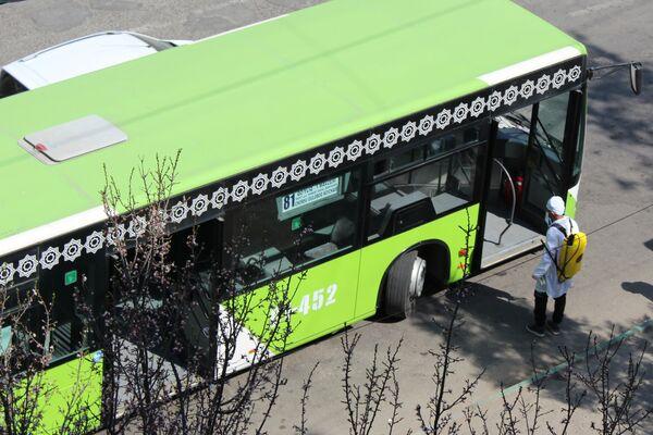 Сотрудник дезинфекионнной службы ждет следующий автобус обработки общее - Sputnik Ўзбекистон