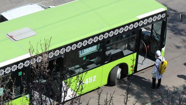 Сотрудник дезинфекионнной службы обрабатывает городские автобусы - Sputnik Узбекистан