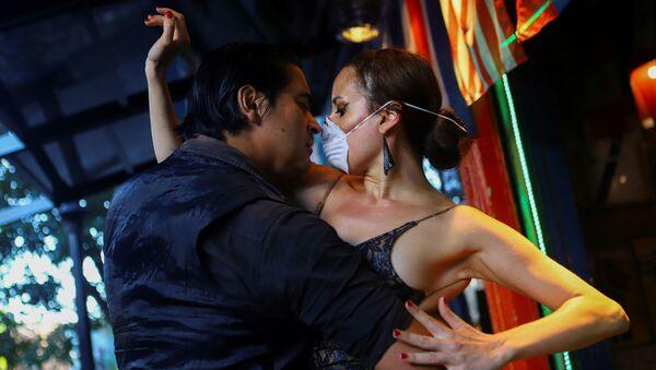 Мужчина и женщина в медицинской маске танцуют танго в почти пустом ресторане в Буэнос-Айресе - Sputnik Ўзбекистон