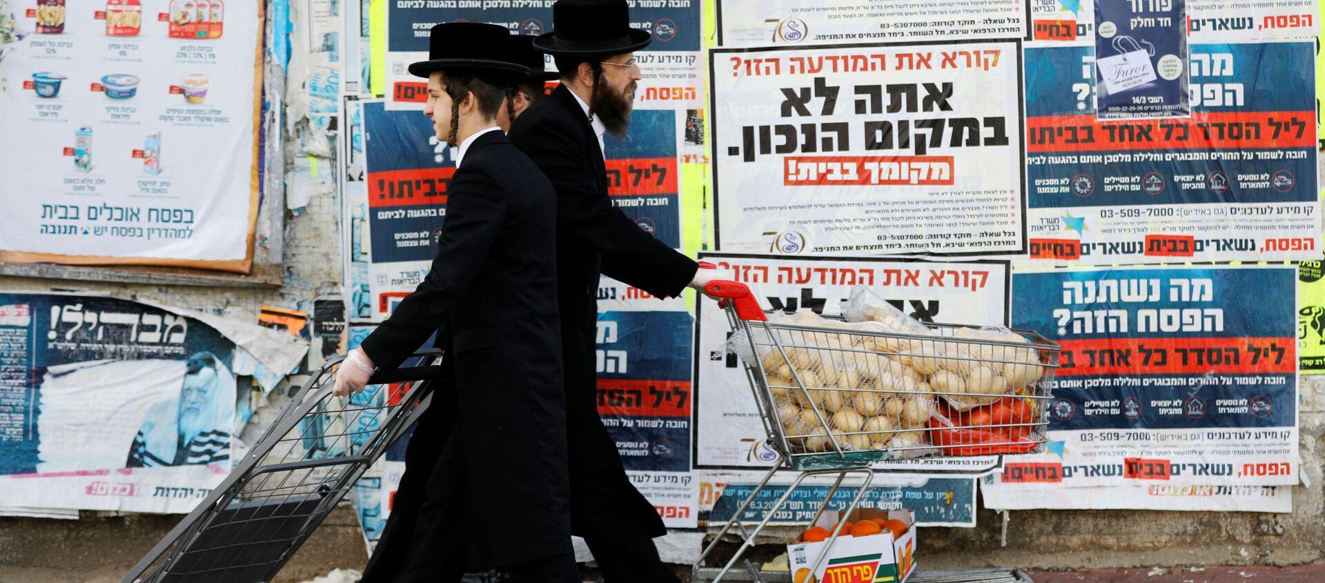 Ультраортодоксальные евреи проходят мимо информационных щитов, призывающих оставаться дома из-за коронавируса в Ашдоде, Израиль - Sputnik Узбекистан, 1920, 21.07.2020