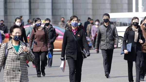 Прохожие в медицинских масках на одной из улиц Пхеньяна, Северная Корея - Sputnik Узбекистан