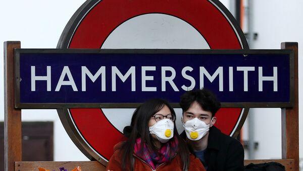 Para v zaщitnыx maskax u stantsii metro Hammersmith v Londone - Sputnik Oʻzbekiston