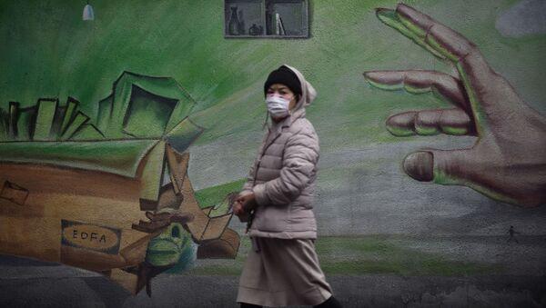 Местная жительница в Ухане, Китай, проходит на фоне стены с граффити - Sputnik Ўзбекистон